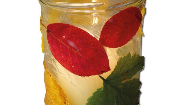 Glas mit bunten Blättern und Kerze